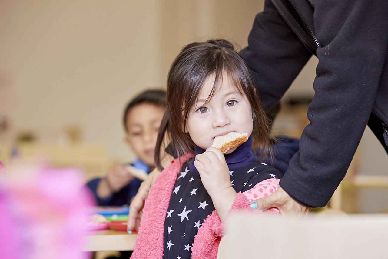 Young child eating sandwich at day care centre